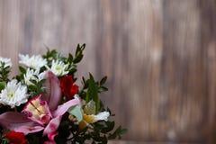 Blumenstrauß von vorzüglichen Blumen auf Holz Lizenzfreie Stockfotos