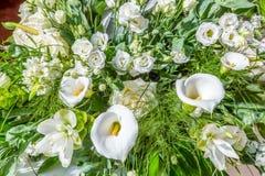 Blumenstrauß von weißen Blumen, von Rosen, von Callalilien und von Grünblättern Lizenzfreie Stockfotos