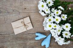 Blumenstrauß von weißen Chrysanthemen mit Umschlag und von zwei blauen Herzen auf Holz Stockfoto