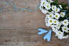 Blumenstrauß von weißen Chrysanthemen mit Umschlag und von zwei blauen Herzen auf Holz Lizenzfreie Stockbilder