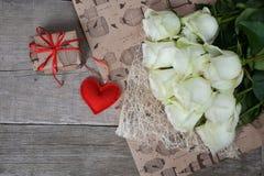 Blumenstrauß von weißen Rosen mit rotem Herzen und Geschenkbox auf hölzernem Hintergrund Lizenzfreies Stockbild