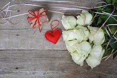 Blumenstrauß von weißen Rosen mit rotem Herzen und Geschenkbox auf hölzernem Hintergrund Lizenzfreies Stockfoto