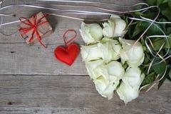 Blumenstrauß von weißen Rosen mit rotem Herzen und Geschenkbox auf hölzernem Hintergrund Lizenzfreie Stockfotos
