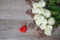 Blumenstrauß von weißen Rosen mit rotem Herzen und von Hagebutten auf hölzernem Hintergrund Stockfoto
