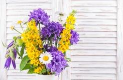 Blumenstrauß von wilden Blumen auf weißem hölzernem Hintergrund Stockbild