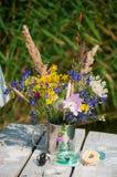Blumenstrauß von wilden Blumen in einer Metallschale mit Flößen Stockbild