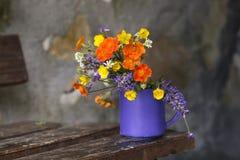 Blumenstrauß von wilden Blumen in einer Schale auf Holzbank lizenzfreie stockfotos