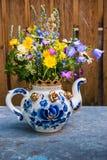 Blumenstrauß von wilden Blumen in einer Teekanne stockbilder
