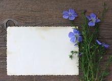 Blumenstrauß von wilden Blumen und von leerer Papierform auf altem Hintergrund Stockbild