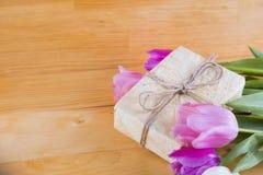 Blumenstrauß von zarten rosa Tulpen mit Geschenkbox auf heller hölzerner Rückseite Stockfotos