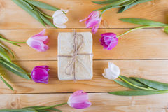 Blumenstrauß von zarten rosa Tulpen mit Geschenkbox auf heller hölzerner Rückseite Stockbilder