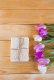 Blumenstrauß von zarten rosa Tulpen mit Geschenkbox auf heller hölzerner Rückseite Stockfoto