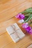 Blumenstrauß von zarten rosa Tulpen mit Geschenkbox auf heller hölzerner Rückseite Lizenzfreies Stockfoto