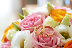 Blumenstraußblumen und Hochzeitsringe Lizenzfreie Stockfotografie