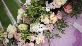 Blumenstraußdekor der künstlichen Blume in der Hochzeitszeremonie mit Unschärfelichthintergrund stock footage