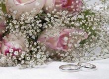 Blumenstraußrosen und Hochzeitsringe Stockfotografie