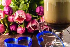 Blumenstraußtulpen und SchalenKaffeetasse, Herz auf Holztisch Lizenzfreie Stockfotos