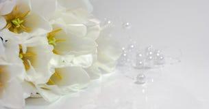 Blumenstrauß von weißen Tulpen mit weißen Perlen auf einer weißen Tabelle stockfoto
