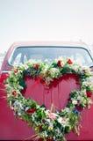 Blumenstrauß auf einem roten Hochzeitsauto Stockfotos