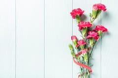 Blumenstrau? der rosa Gartennelke auf h?lzernem Hintergrund des hellen T?rkises lizenzfreie stockbilder