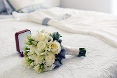 Blumenstrauß und Ringe und Hochzeitskleid Stockbild