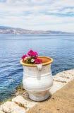Blumentopf über Ägäischem Meer in der Hydra, Griechenland Stockfoto
