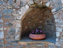 Blumentopf in einer Steine in den Weg gelegte Nische stockbild