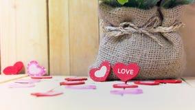 Blumentopf mit Herzen auf hölzerner Tabelle, Valentinsgruß ` s Tageshintergrund Stockfotografie