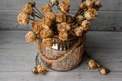 Blumenzusammensetzung des Rosas drückte Rosen in einem Bronzevase, der auf einem hölzernen Brett steht Stilllebenblumenzusammense Stockfotos