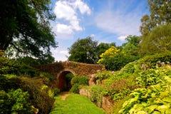 Blumige englische Garten-Szene mit kleinem Brridge stockfotografie