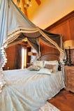 Blumiger Trennvorhang des Betts im klassischen Schlafzimmer Stockfoto