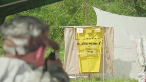 Blur back view of man shooting at yellow aim with animals drawn on it. Man is at left side. stock video