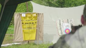 Blur back view of man shooting at yellow aim with animals drawn on it. Man is at right side stock footage