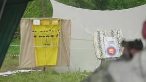 Blur back view of man shooting at yellow aim with animals drawn on it and is on target stock video