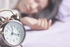 Blur background of Asian woman sleeping in bed. With alarm clock in foreground Stock Images