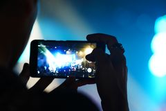 Blur background of cellphone mobilephone photographing concert n. Audience keep taking photo and video at concert with their cellphone focus on the screen with Stock Images