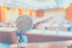 Blur background,close up microphone at podium at Seminar event r. Oom with bokeh light ,Business concept stock photography