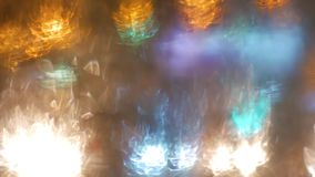 Blur background. Moving bokeh circles of night traffic. Defocused night traffic lights Through the glass in drops of. Rain Thailand. Moving particles. Colorful stock video footage
