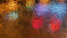 Blur background. Moving bokeh circles of night traffic. Defocused night traffic lights Through the glass in drops of. Rain Thailand. Moving particles. Colorful stock video