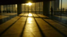 Blur backgrounds of a person walking in business building inside platform,sunset rays light pass window. stock video footage