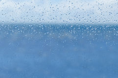 Blur blue water and sky through transparent rainy window Stock Image