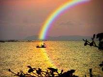Blur boat in sea sunset rainbow sky reflection rainbow on water. Blur boat in sea sunset rainbow on sky and reflection rainbow on water stock images