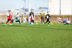 Blur of boys playing soccer. Blur of young kids playing a soccer training match outdoors on an artificial soccer pitch Royalty Free Stock Images