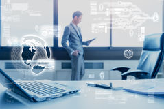 Blur business man standing at window using tablet behind desk. Blur business man standing at window using tablet behind working desk Royalty Free Stock Image