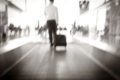 Blur, Businessman dragging a small carry on luggage suitcase. At airport corridor walking to departure gates Stock Images