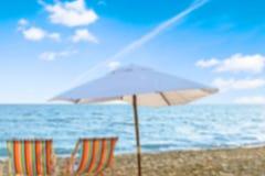 Chaise longue chairs and umbrella on sea beach blur. Blur chairs umbrella chaise longue blue background sky stock photo