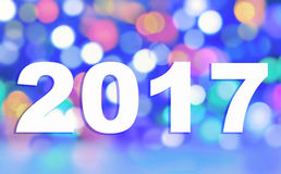 2017 on blur colorful lights. 2017 white figures on blur colorful lights on blue background Stock Photo