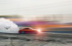 Blur of drifting car with flying drone to shoot picture and video car racing on speed track. stock photo