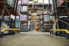 Blur of a forklift truck in the aisle of a warehouse Stock Images