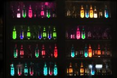 Blur glowing neon light of alcohol drinking bottle in bar or pub for dark night party background. Blur colorful glowing neon light of alcohol drinking bottle in stock images